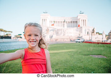 Adorable little girl taking selfie in front of Altare della Patria, Vittoriano, Rome, Italy.