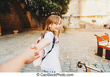 Adorable little girl tourist with backpack on the streets of Provence at sunset. Daughter holding parent's hand, travel with kids.