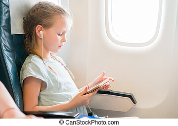 Adorable little girl traveling by an airplane. Cute kid with...