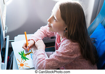 Adorable little girl traveling by an airplane. Kid drawing...