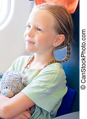 Adorable little girl traveling by an airplane. Kid sitting...
