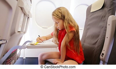 Adorable little girl traveling by plane sitting by aircraft window. Kid drawing picture with colorful pencils.