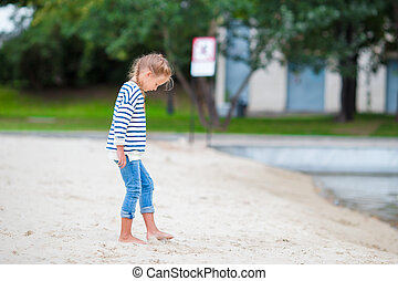 Adorable little girl walking along white sand near the lake
