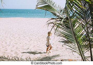Adorable little girl walking at sandy beach
