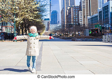 Adorable little girl walking in New York City at spring sunny day