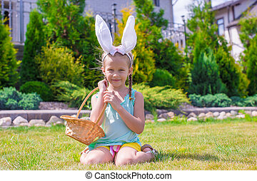Adorable little girl wearing bunny ears holding basket with Easter eggs