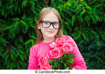 Adorable little girl wearing eyeglasses, holding bright pink roses
