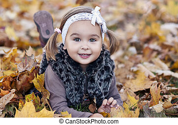 adorable little girl with autumn leaves in the beauty park