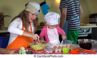 Adorable little girl with chef hat and her young parents preparing cookies