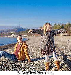Adorable little girl with father having fun on beach in winter warm day