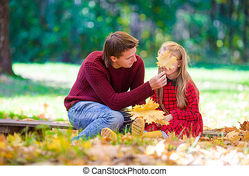 Adorable little girl with father in autumn park outdoors