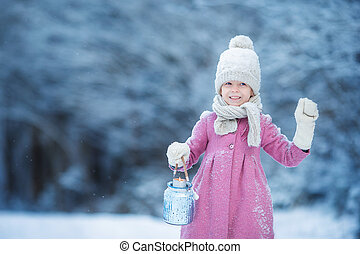 Adorable little girl with flashlight in cold day on Christmas outdoors