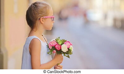 Adorable little girl with flowers bouquet walking in european city outdoors