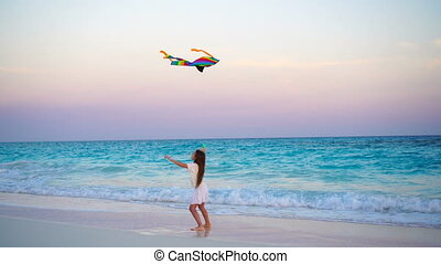 Adorable little girl with flying kite on tropical beach at sunset. Kids play on ocean shore. Child with beach toys.