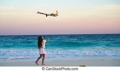 Adorable little girl with flying kite on tropical beach. Happy kid playing on ocean shore with beach kite. Slow moion