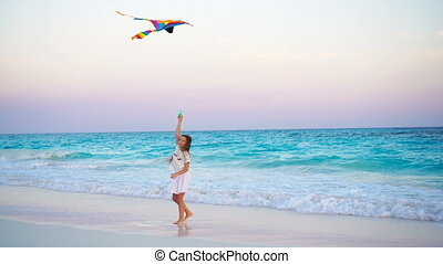 Adorable little girl with flying kite on tropical beach. Kid play on ocean shore with beautiful sunset