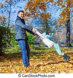 Adorable little girl with happy dad having fun in autumn park on a sunny day