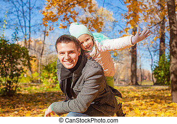 Adorable little girl with happy dad having fun in autumn park on sunny day