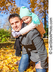 Adorable little girl with happy father having fun in autumn park on a sunny day