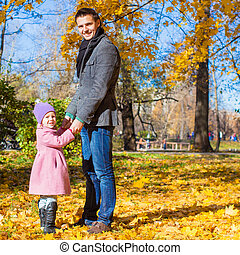 Adorable little girl with happy father in park at autumn