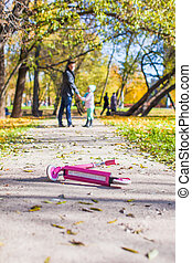 Adorable little girl with happy father walking in autumn park on a sunny day
