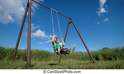Adorable little girl with her beautiful mother having fun on a swing outdoor