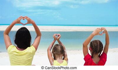 Adorable little girls and young mother showing hearts on...