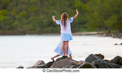 Adorable little girls have a lot of fun on the beach. Two beautiful kids are happy