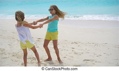 Adorable little girls have fun together on white tropical...