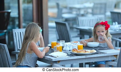 Adorable little girls having breakfast at outdoor cafe
