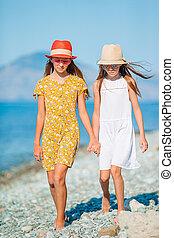 Adorable little girls having fun on the beach