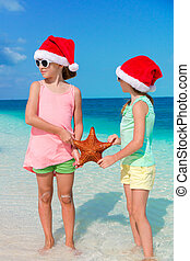 Adorable little girls on Christmas beach vacation. Kids with...
