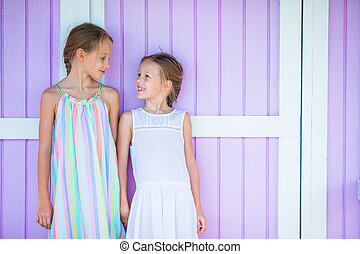 Adorable little girls on summer vacation background traditional colorful caribbean house