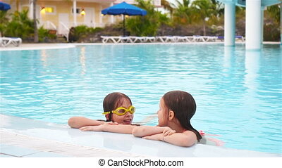 Adorable little girls playing in outdoor swimming pool...