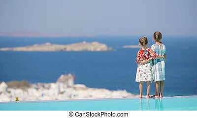 Adorable little girls playing in the edge of outdoor swimming pool with amazing view of old Mykonos town, Europe