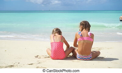 Adorable little girls playing with sand on the beach. Back...