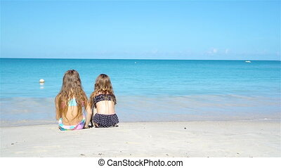 Adorable little girls playing with sand on the beach. Kids...