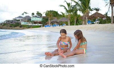Adorable little girls playing with sand on the beach.