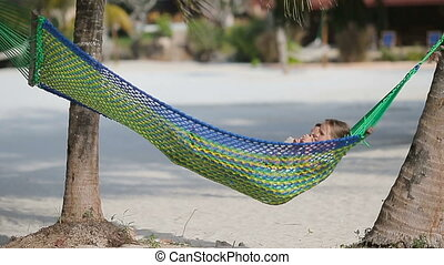 Adorable little girls relaxing in hammock on the beach
