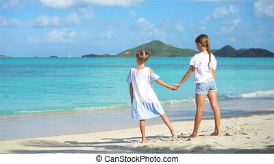 Adorable little girls walking on the beach and having fun...