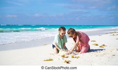 Adorable little kids play with sand on the white beach