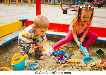 Adorable little kids playing in a sandbox