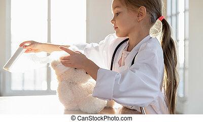 Adorable little preschooler bandaging head of teddy bear.