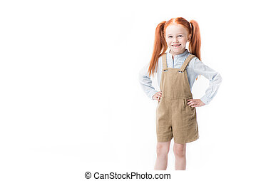 Adorable little redhead girl standing with hands on waist and smiling at camera isolated on white