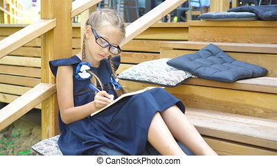 Adorable little school girl with notes and pencils outdoor. Back to school.