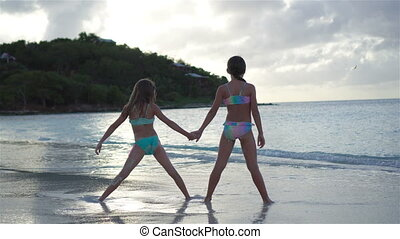 Adorable little sisters at beach during summer vacation -...