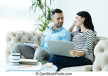 Adorable millennial couple looking at each other while working