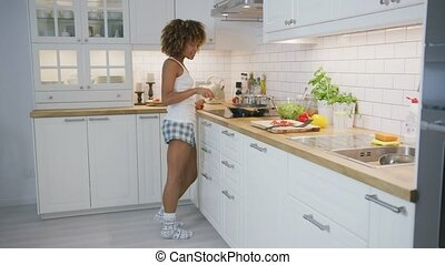 Adorable model dancing happily while cooking