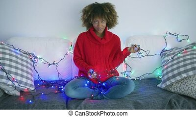 Adorable model with garland on sofa - Content woman in red...