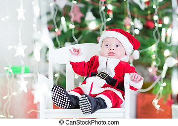 Adorable newborn baby boy in Sante outfit sitting in a white cha